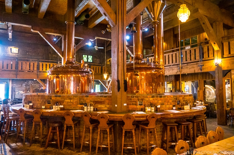 stools surrounding two golden beer vats surrounded by bricks