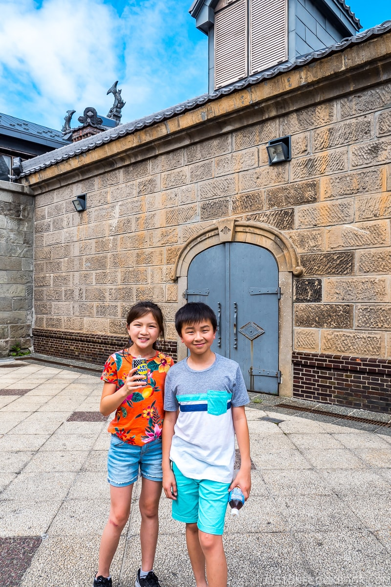 two children in a courtyard in front of a stonewall