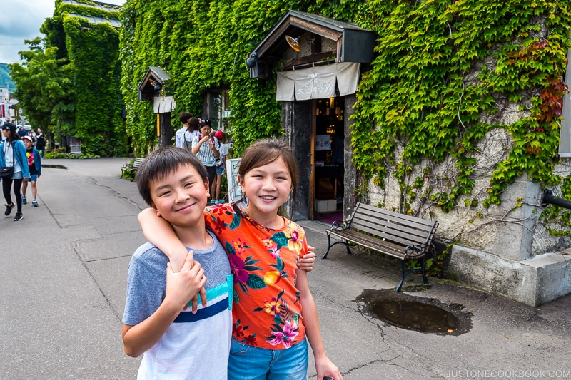 two children in front of stone building covered in ivy