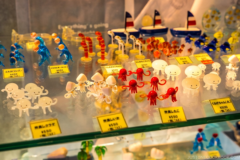assorted creatures made from glass on a glass shelf