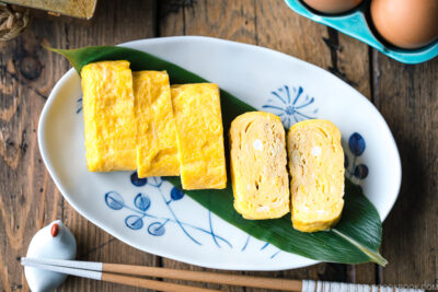 An oval plate containing Japanese sweet rolled omelet.