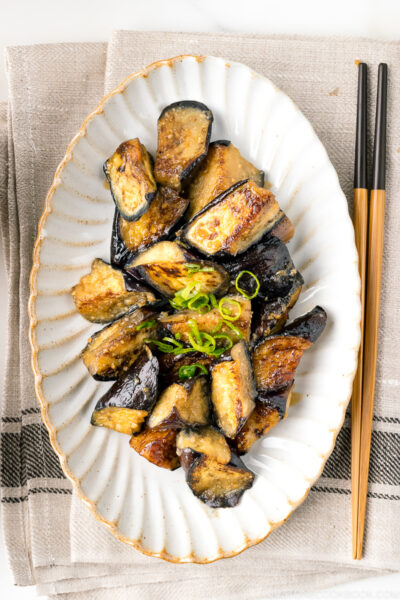 A white oval ceramic plate containing stir fry miso eggplant garnished with scallion.