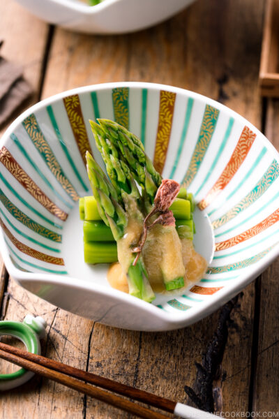 A shell shaped bowl containing Asparagus with Miso Dressing (Karashi Sumisoae) garnished with salt pickled cherry blossom.