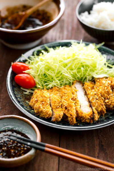 A plate containing baked tonkatsu, shredded cabbage, and cherry tomatoes.