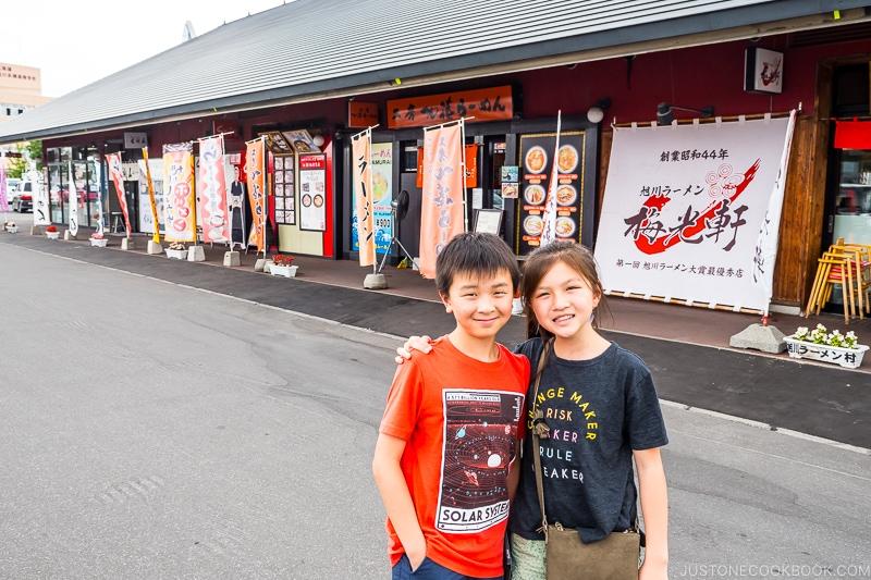 two children standing in front of ramen village