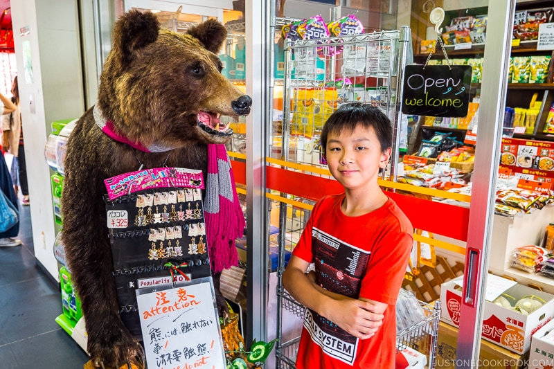 boy standing next to a bear next to a gift shop
