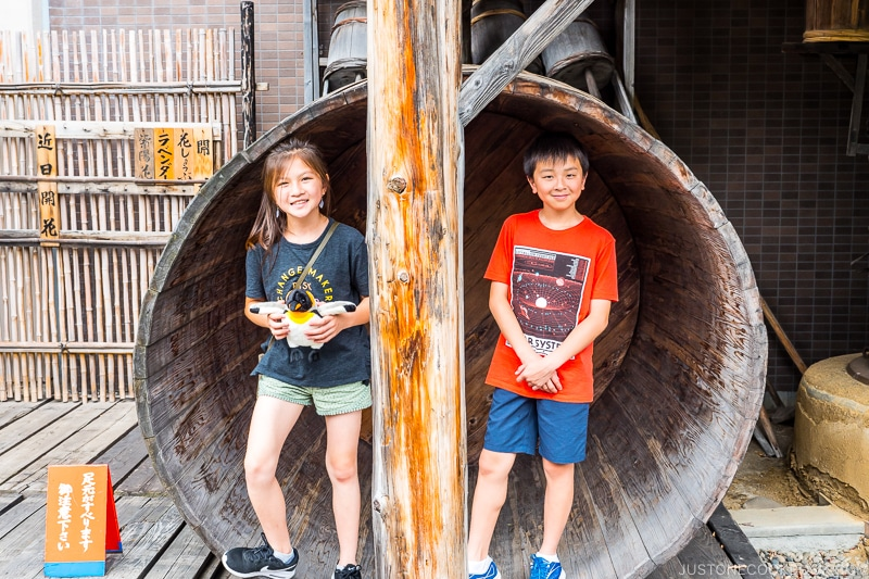 two children standing in a large wood vat