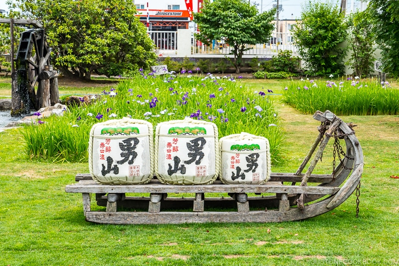 sake barrels on a sled on top of grass in a garden