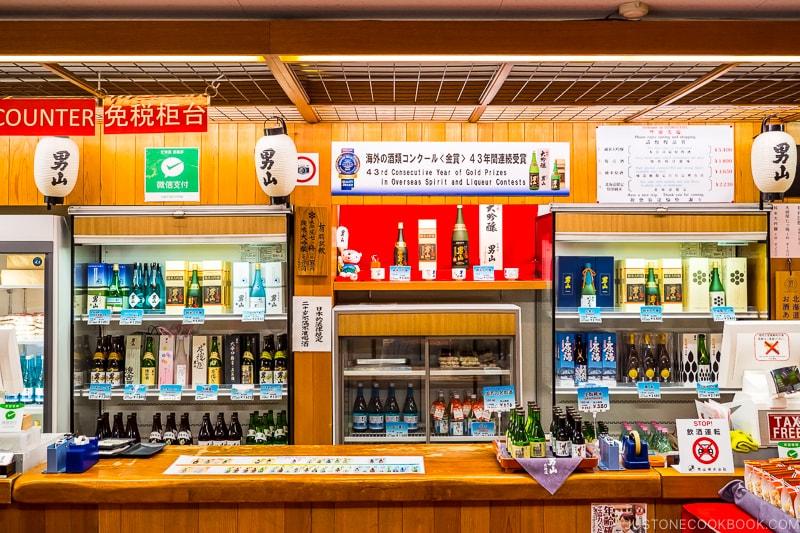 the tasting room with sake bottles along the back wall at Otokoyama Sake Brewery Museum in Asahikawa