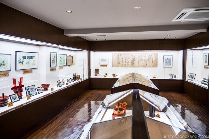sake museum with sake making tools on display behind glass