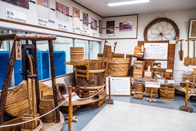 historical sake making tools on display along the wall including various size vats