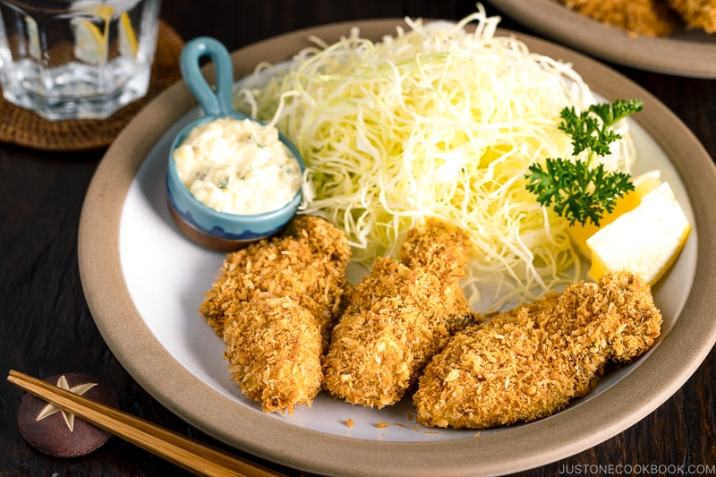 A plate containing fried oyster (kaki furai) along with shredded cabbage and tartar sauce.