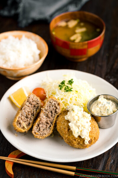 A plate containing menchi katsu (ground meat cutlet) along with shredded vegetables and tartar sauce.