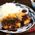 A plate containing Tonkatsu, shredded cabbage, and a small bowl of miso sauce.