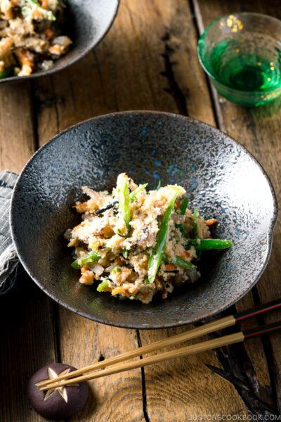 A black bowl containing Okara (Unohana) mixed with assorted vegetables, shiitake mushroom, seaweed, and konnyaku.