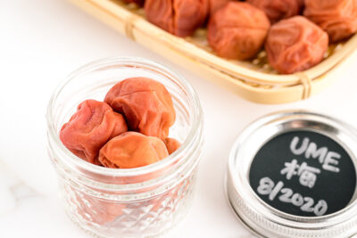A glass jar and a bamboo strainer containing umeboshi (Japanese pickled plums).