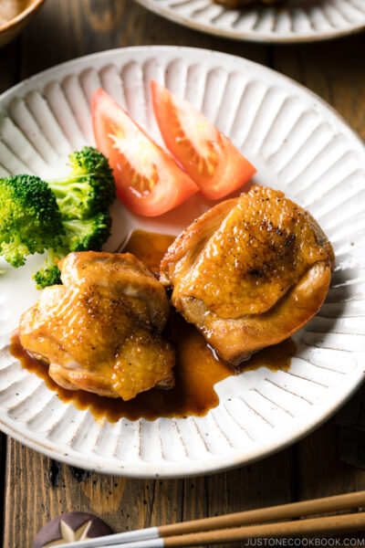 A plate containing butter shoyu chicken, broccoli, and tomatoes.