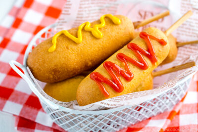 A basket containing corn dogs served with ketchup and mustard drizzle.