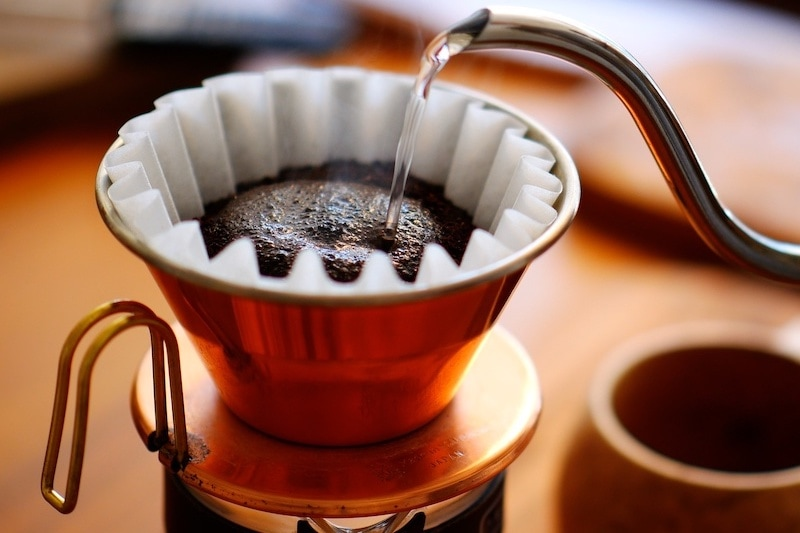 image of pouring hot coffee over charcoal roasted coffee in a coffee filter maker