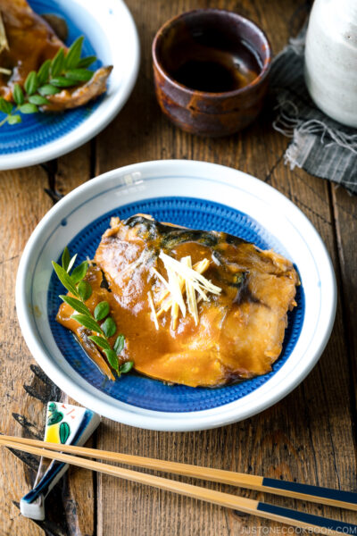 A blue Japanese plate containing Saba Misoni (Mackerel Simmered in Miso) garnished with julienned ginger.