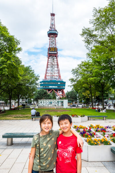 two children standing in front of Sapporo TV Tower