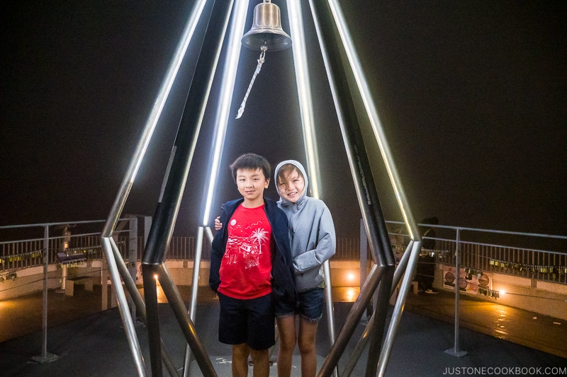 two children standing in a lighted metal structure