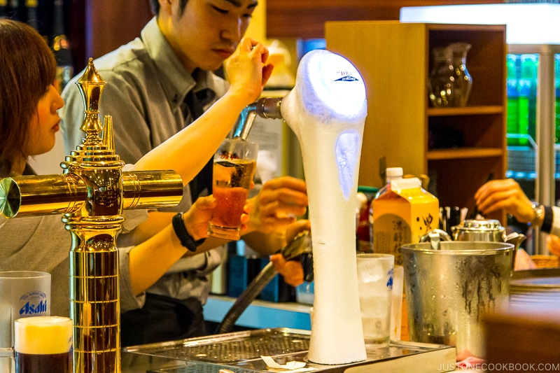 worker pour Asahi beer from tap