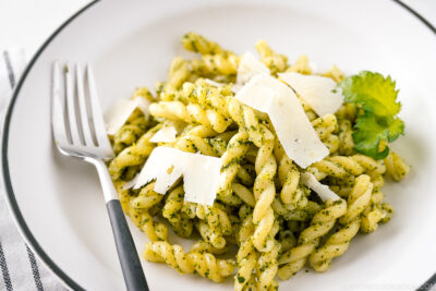 A white bowl containing Shiso Pesto Pasta garnished with shaved Parmesan cheese and shiso leaves.