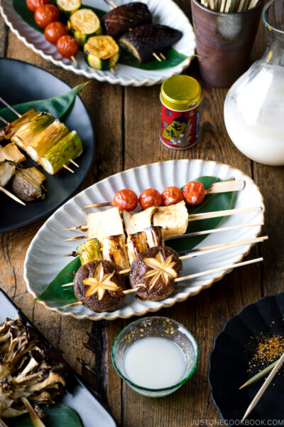 A ceramic plate containing Yakitori Style Grilled Vegetables along with Nigori Sake.