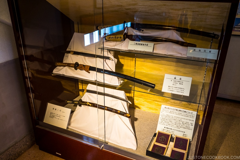 a collection of swords in a glass display case