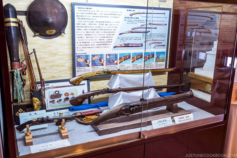 a collection of antique guns in a display case