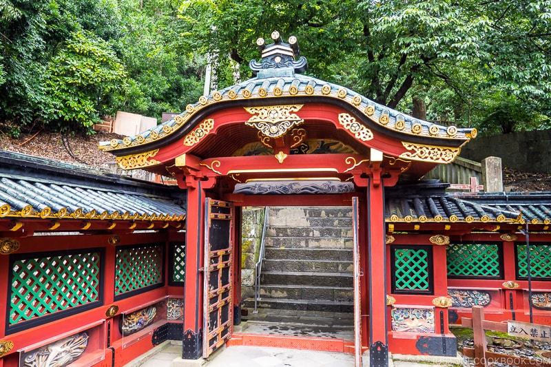 ornate red gate with stone steps in the back