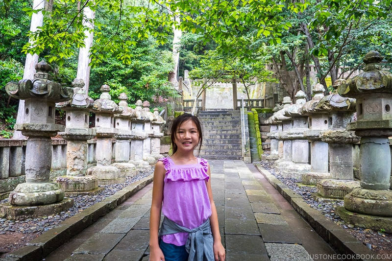 a girl standing on a stone path with stone lanterns on the side