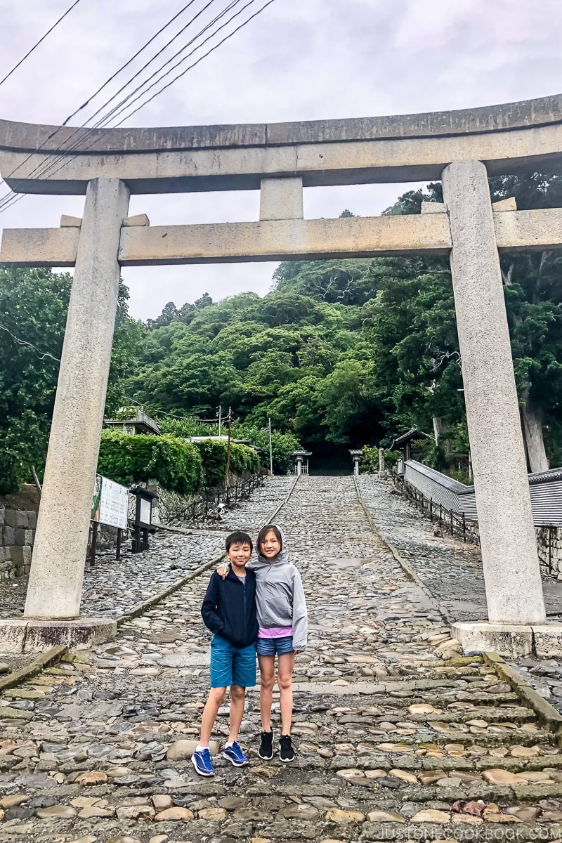 two children standing under a large stone torii gate