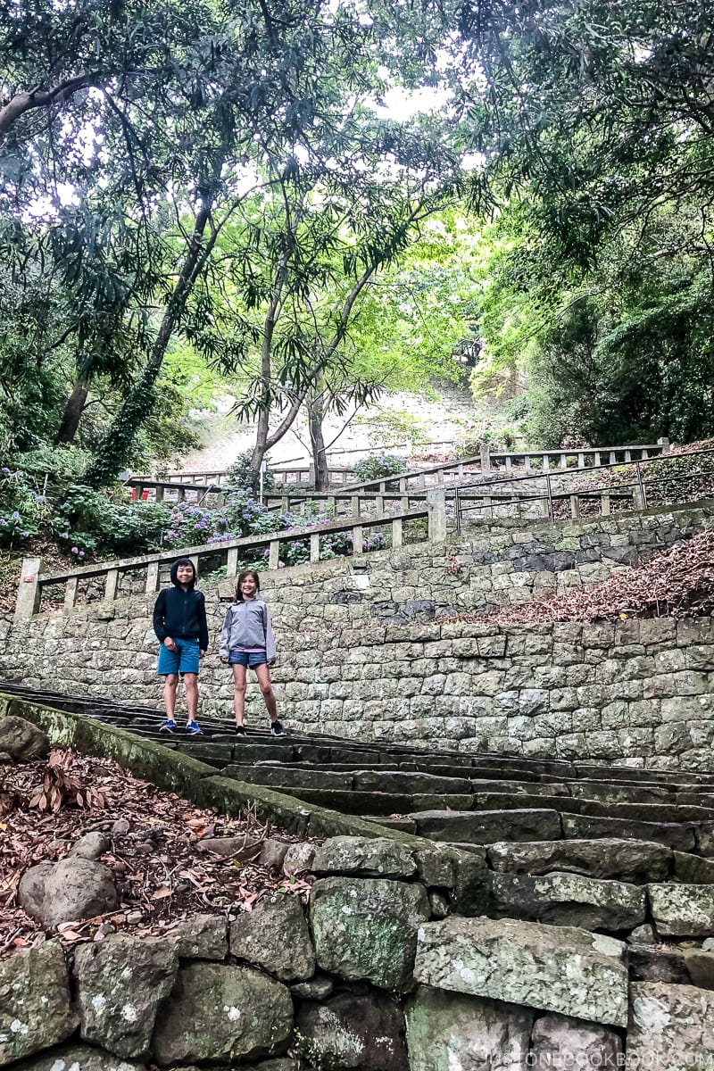two children standing on stone steps with zig zag incline behind themn