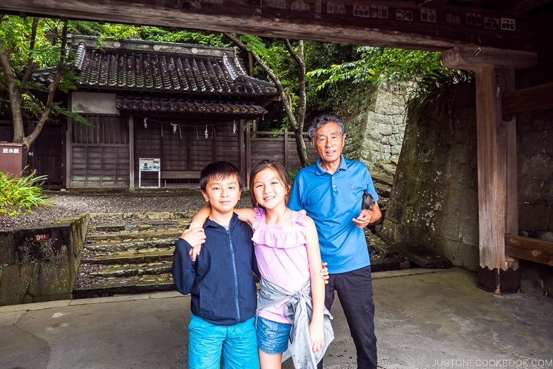 two children with an older man standing in front of a shrine structure
