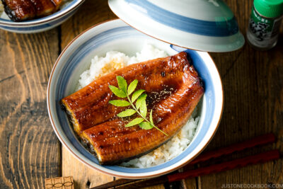 A donburi bowl containing grilled eel fillet over steamed rice.