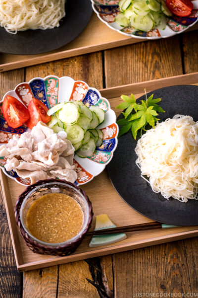 A wooden tray containing a plate of somen noodles, a bowl of sesame miso dipping sauce, and a plate of pork shabu shabu and cucumber slices.