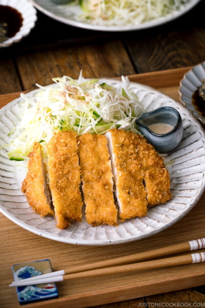 A Japanese ceramic containing Tonkatsu (pork cutlet) and shredded cabbage salad.