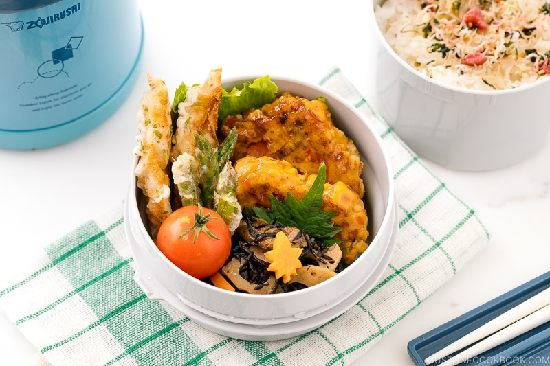 A Zojirushi lunch jar containing steamed rice, chicken meatballs, asparagus tempura, and hijiki salad.