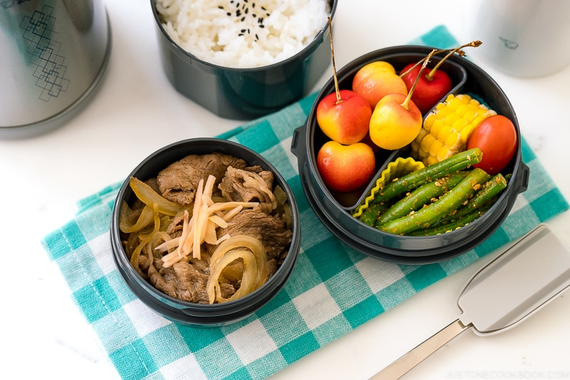 A Zojirushi lunch jar containing steamed rice, gyudon, fruits, and green bean gomaae.
