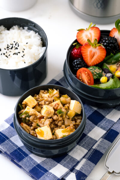 A Zojirushi lunch jar containing steamed rice, mapo tofu, fruits, and salad.