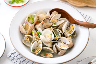 A ceramic bowl containing Japanese Sake-Steamed Clams.