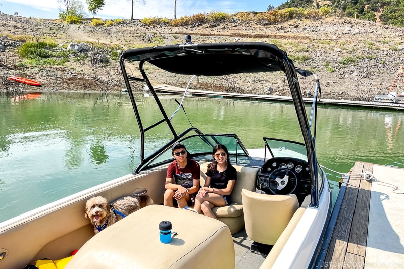 two children and a dog inside a boat on a lake