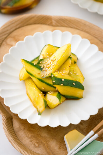 A white plate containing Spicy Japanese Pickled Cucumbers sprinkled with white sesame seeds.