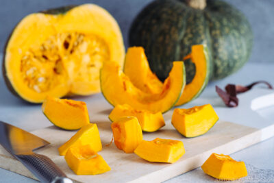 Kabocha being cut with a knife on a wooden cutting board.