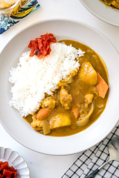 A ceramic bowl containing Japanese Chicken Curry along with steamed rice and fukujinzuke pickles.